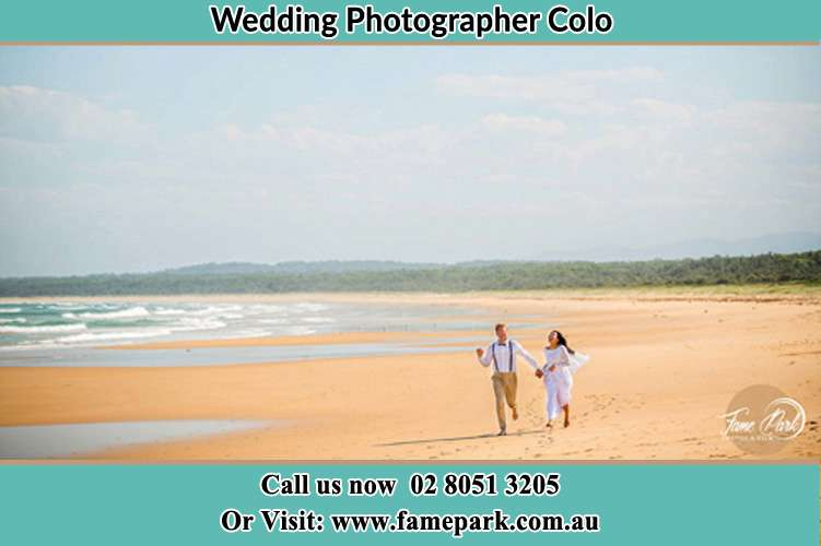 Photo of the Groom and the Bride walking at the sea front Colo NSW 2756