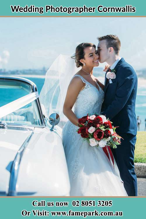 Photo of the Groom kiss the Bride besides the bridal car Cornwallis NSW 2756