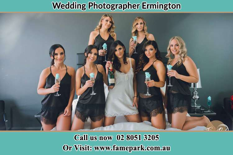 Photo of the Bride and the bridesmaids wearing lingerie and holding glass of wine on bed Ermington NSW 2115