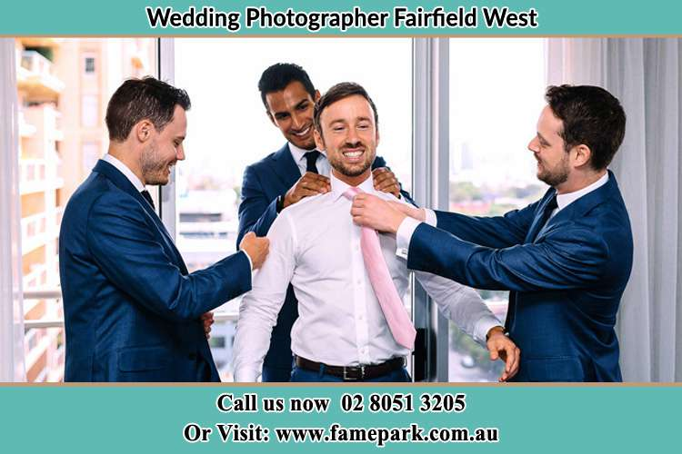 Photo of the Groom helping by the groomsmen getting ready Fairfield West NSW 2165
