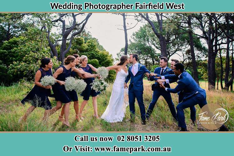 Photo of the Bride and the Groom kissing while teasing by the entourage Fairfield West NSW 2165