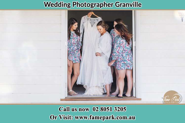 Photo of the Bride and the bridesmaids checking the wedding gown at the front door Granville NSW 2142