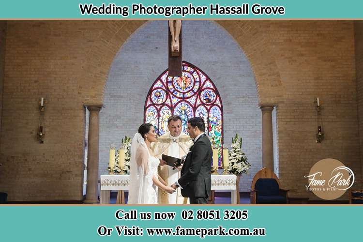 Photo of the Bride and Groom at the Altar with the Priest Hassall Grove NSW 2761