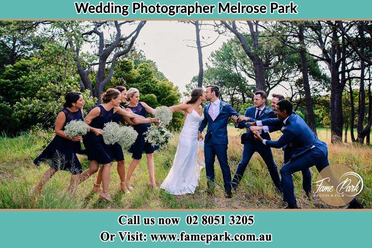 Photo of the Bride and the Groom kissing while teasing by the entourage Melrose Park NSW 2114