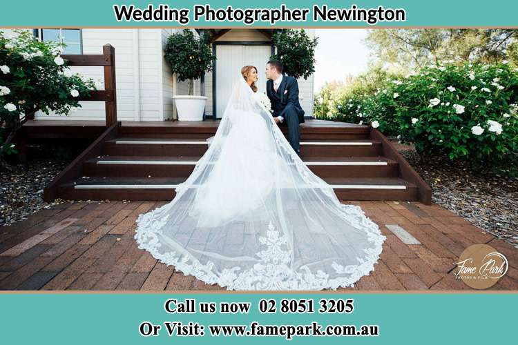 Photo of the Bride and the Groom looking each other while sitting at the staircase Newington NSW 2127