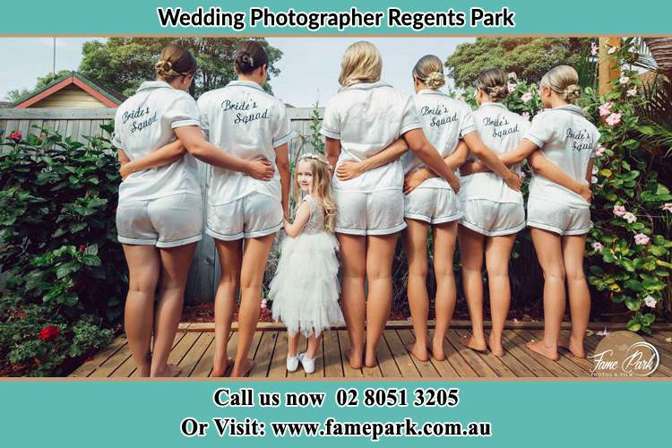 Behind photo of the Bride and the bridesmaids with the flower girl looking back Regents Park NSW 2143
