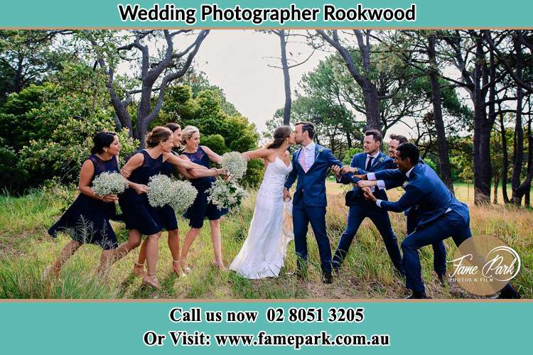 Photo of the Bride and the Groom kissing while teasing by the entourage Rookwood NSW 2141