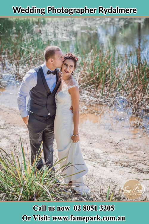 Photo of the Groom kiss the Bride near the lake Rydalmere NSW 2116