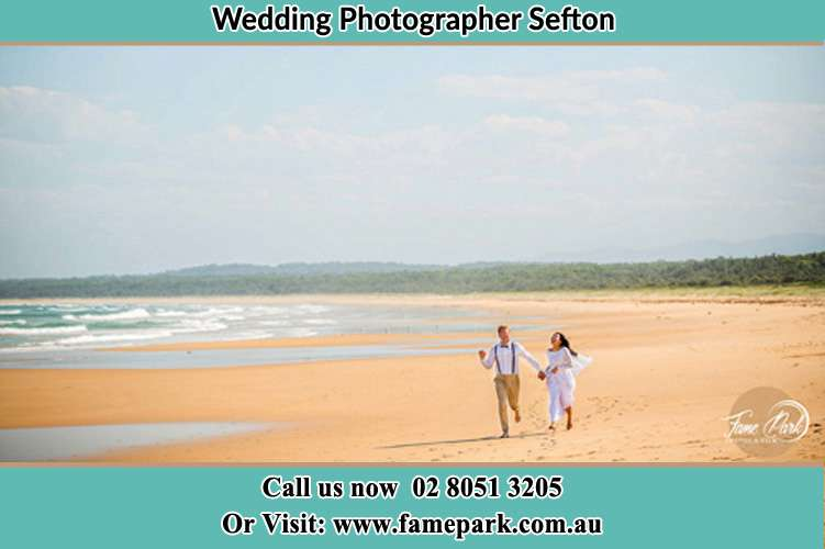 Photo of the Groom and the Bride walking at the sea shore Sefton NSW 2162