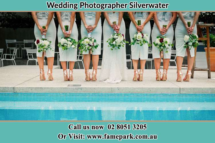 Behind photo of the Bride and the bridesmaids holding flowers near the pool Silverwater NSW 2128