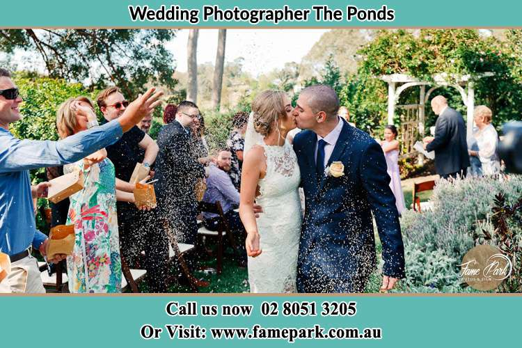 Photo of the Bride and the Groom kissing while showering rice by the visitors The Ponds NSW 2769