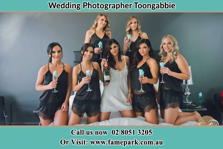 Photo of the Bride and the bridesmaids wearing lingerie and holding glass of wine on bed Voyager Point NSW 2172