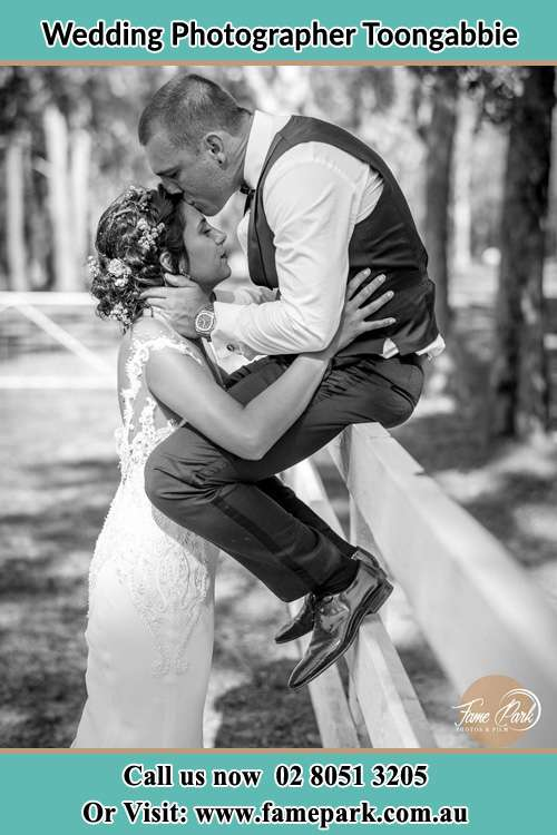 Photo of the Groom sitting on the fence while kissing the Bride on the forehead Voyager Point NSW 2172